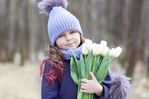 Menina bonita no parque com um buquê de tulipas brancas. buquê de tulipas. flores como um presente para o dia das mães das mulheres. 8 de março. o conceito de primavera e o dia da mulher. páscoa. closeup retrato criança Foto Premium