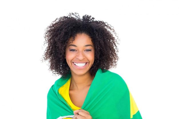 Menina bonita no tshirt amarelo que guardara a bandeira brasileira que sorri na câmera Foto Premium