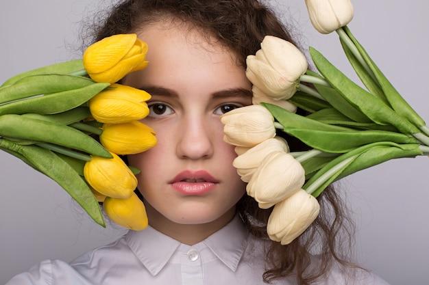 Menina bonita no vestido com tulipas flores nas mãos Foto Premium