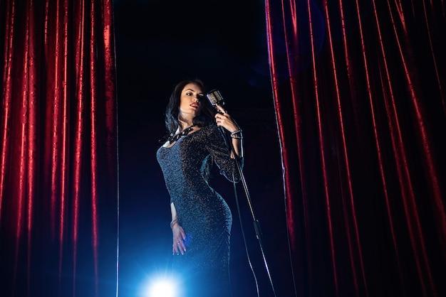 Menina bonita no vestido preto, cantando no microfone na sala de concertos Foto Premium