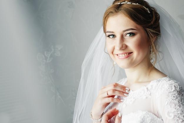 Menina bonita, noiva em um vestido branco no fundo do apartamento. casamento, reunião de noiva, criação de família. Foto Premium