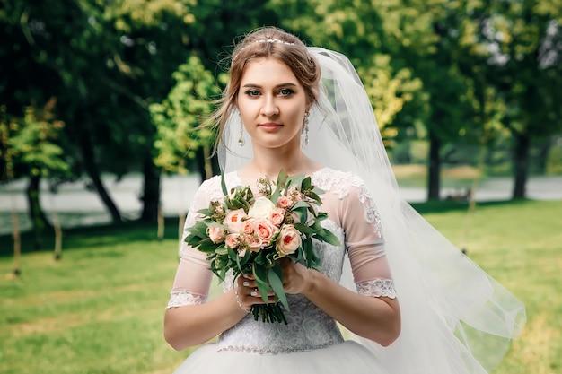 Menina bonita, noiva em um vestido de casamento branco em um fundo da natureza verde. casamento, criação familiar. Foto Premium
