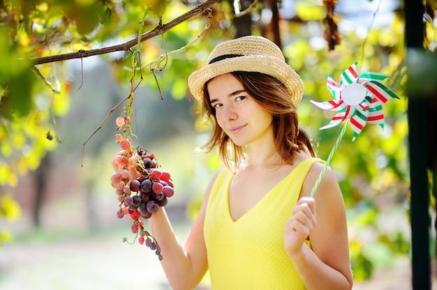 Menina bonita nova que escolhe a uva madura no dia ensolarado em itália. feliz fazendeiro feminino trabalhando no pomar de fruta Foto Premium