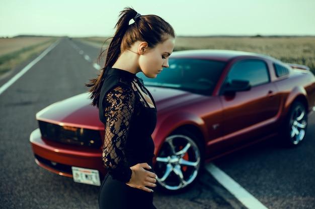 Menina bonita nova que levanta perto do carro vermelho caro, carro poderoso Foto gratuita