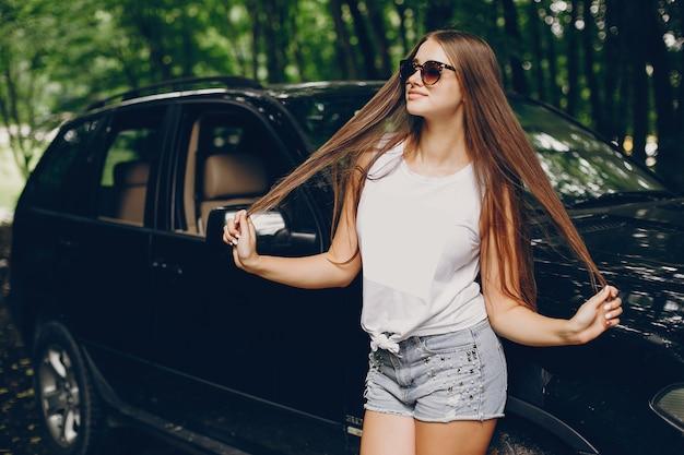 Menina bonita perto de um carro Foto gratuita