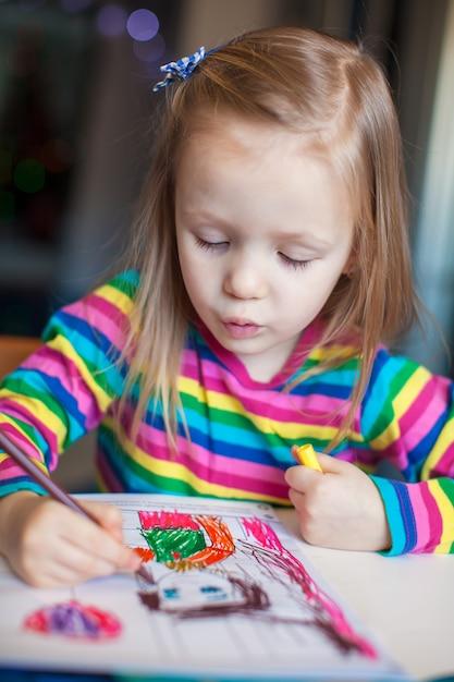 Menina bonita pintura com lápis enquanto está sentado na sua mesa Foto Premium