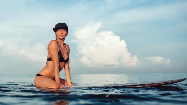 Menina bonita posando sentado em uma prancha de surf no oceano Foto gratuita