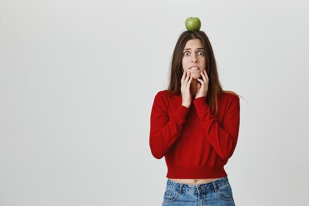 Menina bonita preocupada e alarmada, segurando o alvo de maçã na cabeça e esperando o arqueiro fazer tiro, morder o lábio nervoso Foto gratuita
