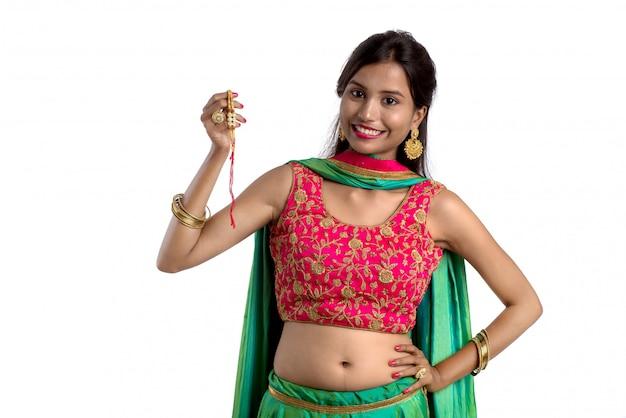 Menina bonita que mostra rakhi por ocasião de raksha bandhan em um fundo branco. a irmã amarra rakhi como símbolo de intenso amor por seu irmão. Foto Premium