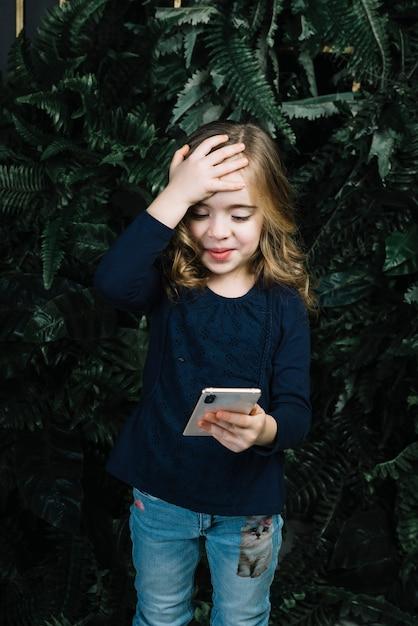 Menina bonita que olha o telefone esperto que põe a mão sobre sua cabeça Foto gratuita