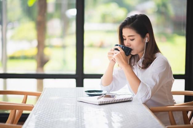 Menina bonita que trabalha no café e beber um pouco de café Foto Premium