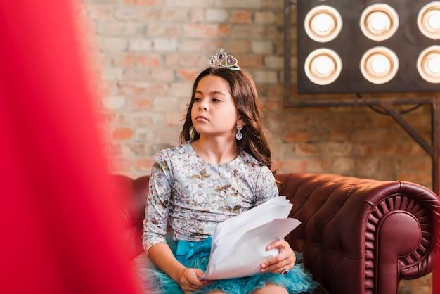 Menina bonita segurando scripts sentado no sofá olhando para longe Foto gratuita