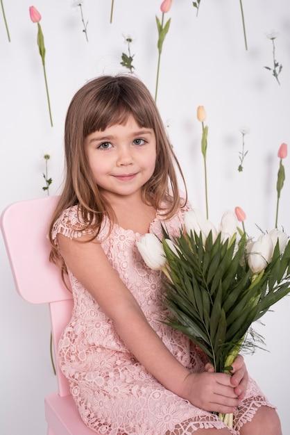 Menina bonita segurando tulipas tiro médio Foto gratuita