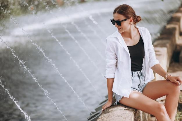 Menina bonita sentada junto às fontes Foto gratuita