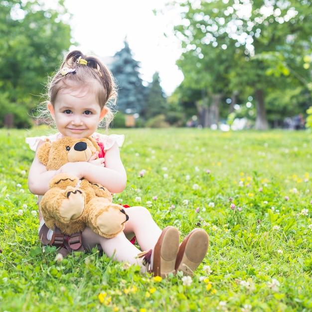 Menina bonita sentada na grama verde, abraçando seu ursinho de pelúcia Foto gratuita