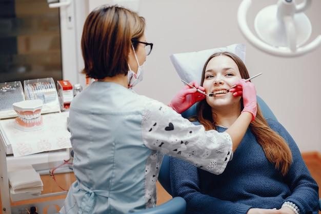 Menina bonita sentada no consultório do dentista Foto gratuita