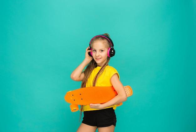 Menina bonita skatista segurando o skate Foto gratuita