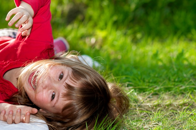 Menina bonita sorridente criança bonita com olhos cinzentos e cabelos louros longos se divertindo ao ar livre, deitado na grama verde no campo ensolarado verde verão turva. beleza, sonhos e jogos de infância. Foto Premium