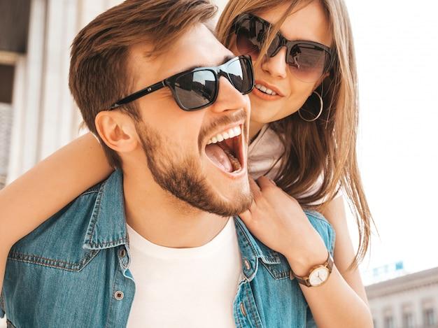 Menina bonita sorridente e seu namorado bonito em roupas de verão casual. homem carregando sua namorada nas costas e ela levantando as mãos. Foto gratuita