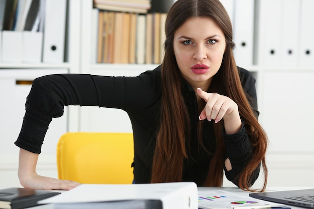 Menina bonita sorridente funcionário no local de trabalho falar com o visitante Foto Premium