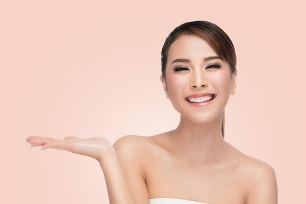 Menina bonita spa mostrando vazio palma da mão aberta para o texto na cor rosa com traçado de recorte Foto Premium