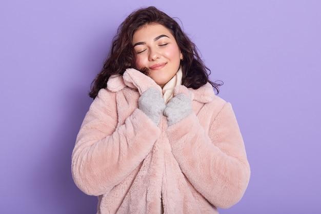 Menina bonita vestindo casaco de pele sintética rosa pálido Foto gratuita
