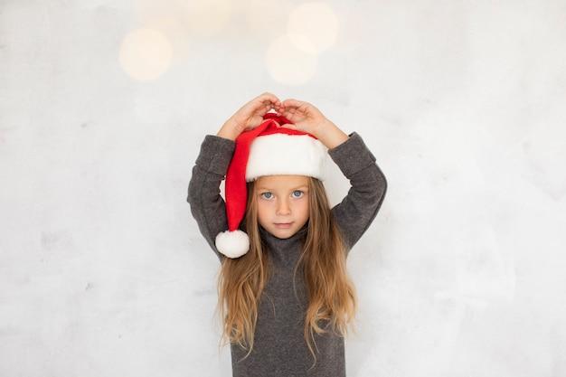 Menina bonita, vestindo um chapéu de papai noel Foto gratuita