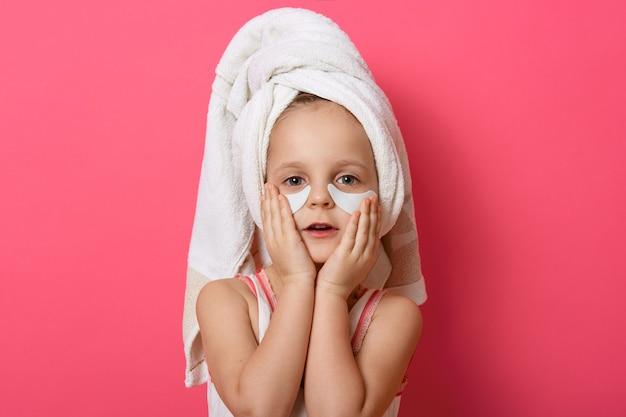 Menina bonita, vestindo uma toalha branca na cabeça, posando com manchas sob os olhos Foto gratuita