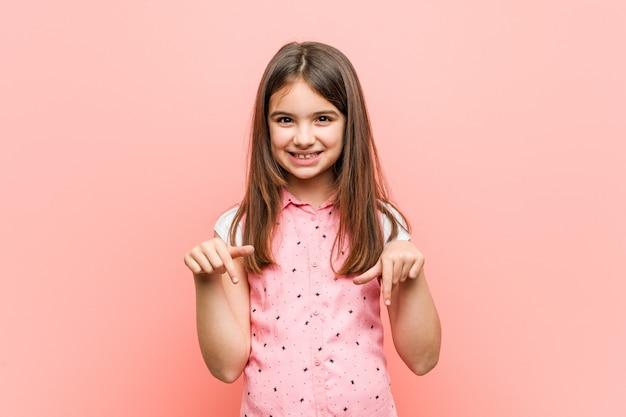 Menina bonitinha aponta para baixo com os dedos, sentimento positivo. Foto Premium