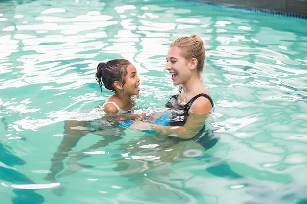 Menina bonitinha aprendendo a nadar com o treinador Foto Premium