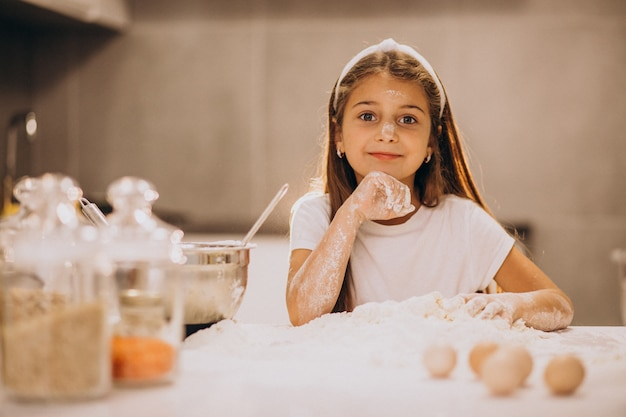 Menina bonitinha assando na cozinha Foto gratuita