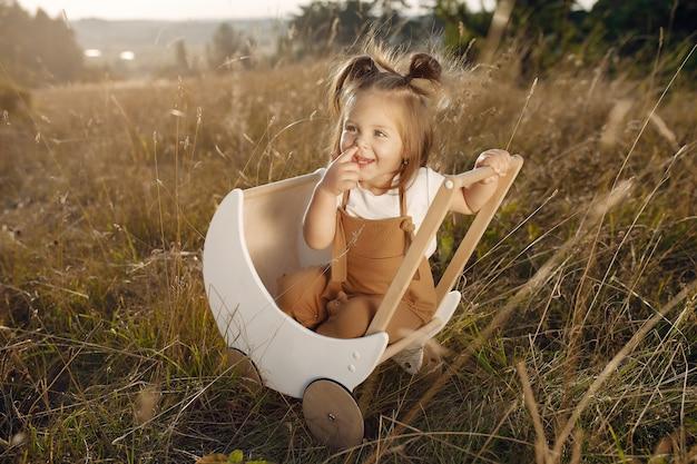 Menina bonitinha brincando em um parque com carruagem branca Foto gratuita