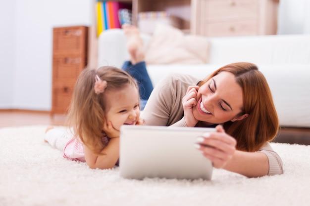Menina bonitinha com a mãe usando tablet digital em casa Foto gratuita