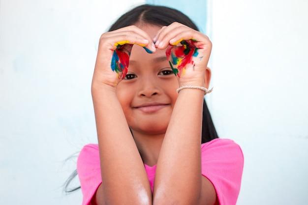 Menina bonitinha com mãos pintadas coloridas na parede Foto Premium
