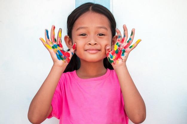 Menina bonitinha com mãos pintadas coloridas no fundo da parede Foto Premium