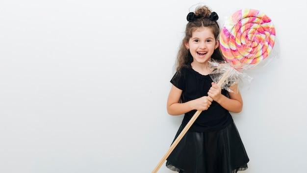 Menina bonitinha com pirulito gigante e cópia espaço Foto gratuita