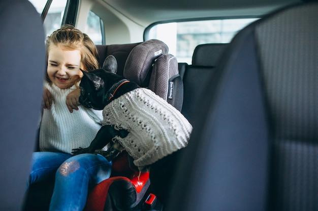 Menina bonitinha com seu animal de estimação sentado na parte de trás de um carro Foto gratuita