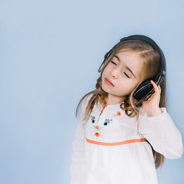 Menina bonitinha curtindo a música no fone de ouvido contra o fundo azul Foto gratuita