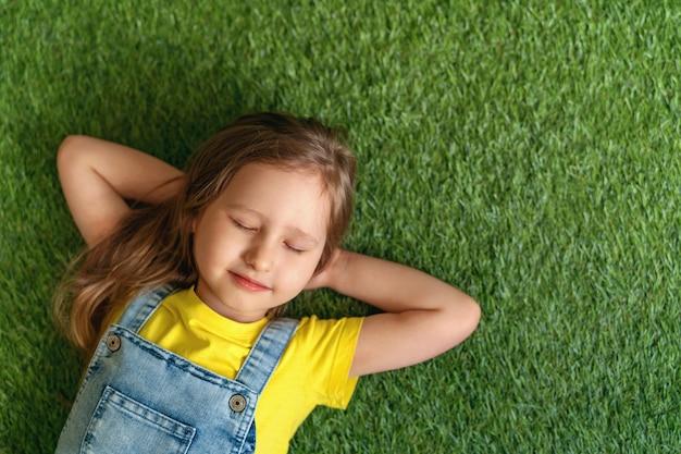 Menina bonitinha de macacão jeans, deitado no tapete verde, gramado fechou os olhos Foto Premium