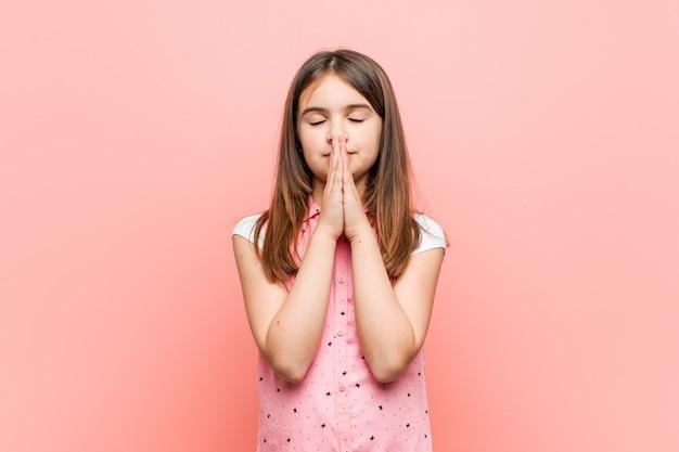 Menina bonitinha de mãos dadas em rezar perto da boca, sente-se confiante. Foto Premium