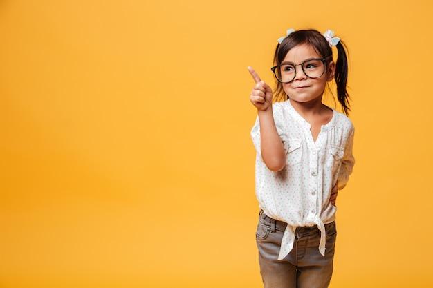 Menina bonitinha de óculos apontando. Foto gratuita