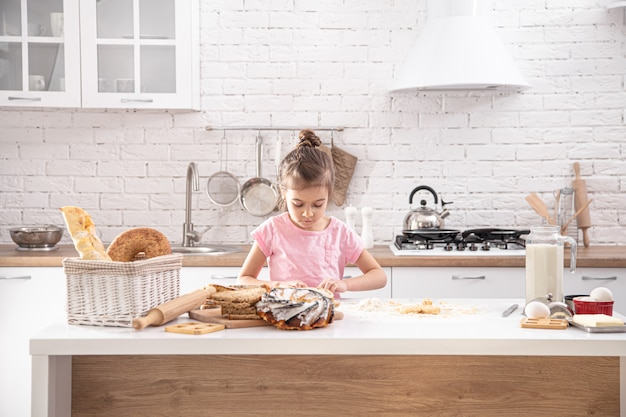 Menina bonitinha é cozinhar bolos caseiros na cozinha. Foto gratuita