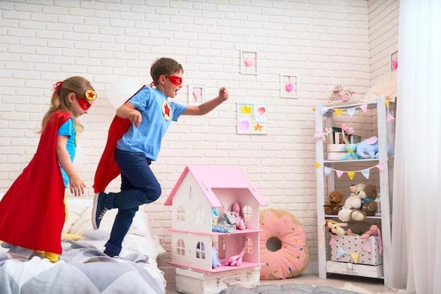 Menina bonitinha e garoto pulando da cama para voar Foto Premium
