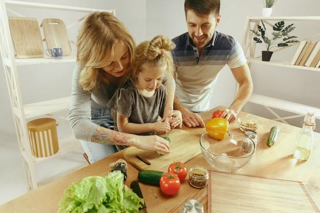 Menina bonitinha e seus lindos pais estão cortando legumes e sorrindo enquanto fazem salada na cozinha em casa. conceito de estilo de vida familiar Foto gratuita