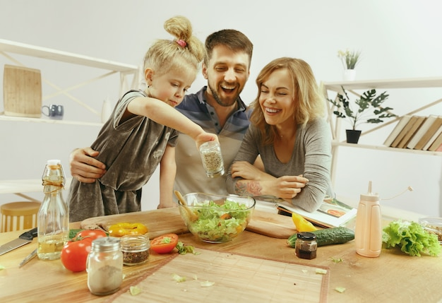 Menina bonitinha e seus lindos pais estão cortando vegetais e sorrindo enquanto fazem salada na cozinha de casa Foto gratuita