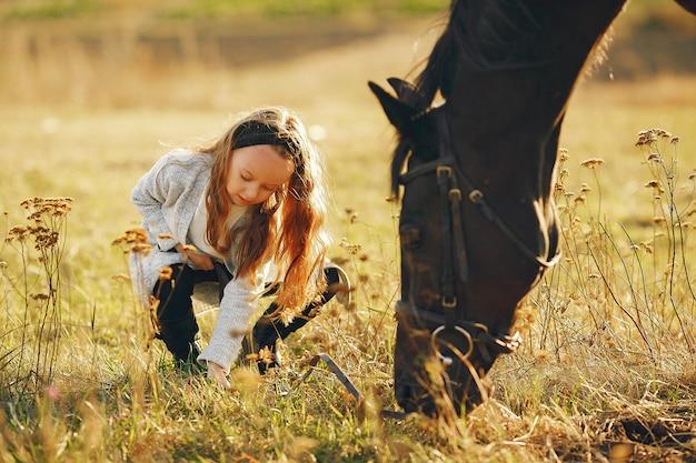 Menina bonitinha em um campo de outono com cavalo Foto gratuita