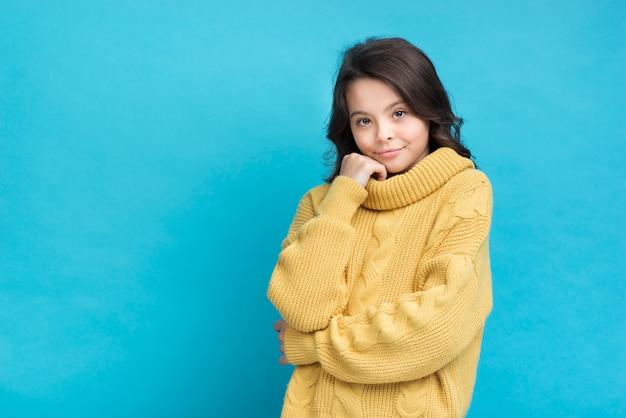 Menina bonitinha em um suéter amarelo sobre fundo azul Foto gratuita