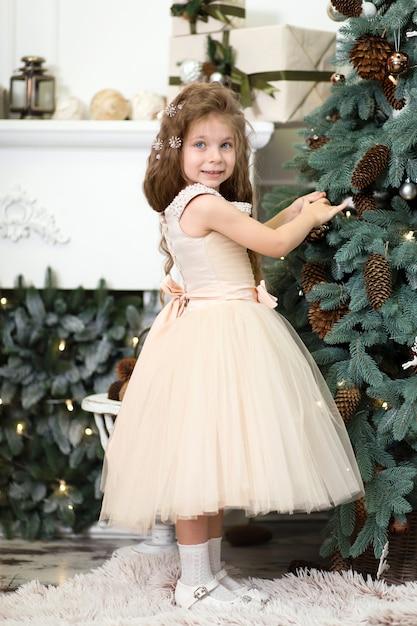 Menina bonitinha em um vestido bege exuberante trava cones na árvore de natal que está de pé em casa Foto Premium