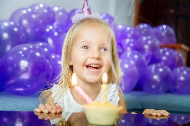 Menina bonitinha em vestido elegante, comemorando o dia do aniversário com balões roxos Foto Premium