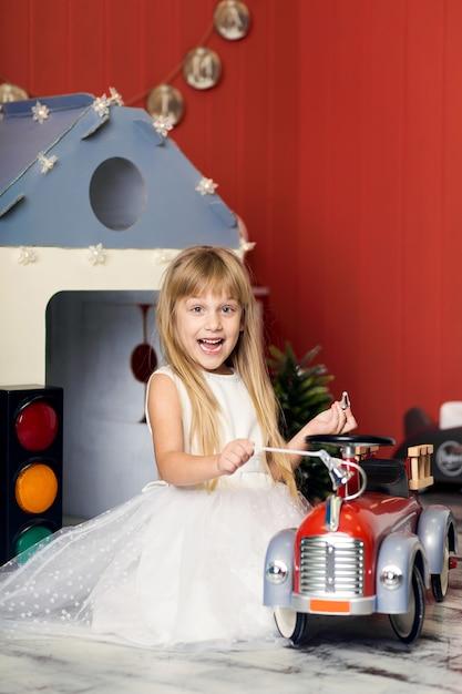 Menina bonitinha está brincando com um caminhão de bombeiros de brinquedo grande Foto Premium